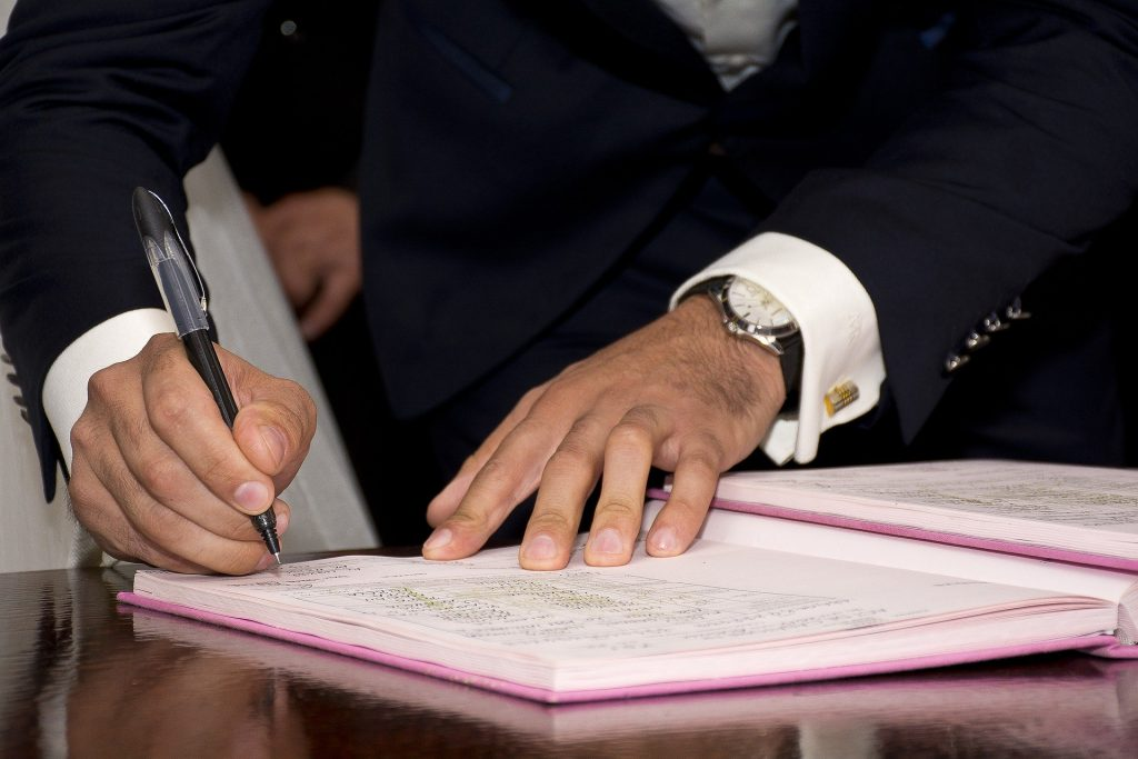 a man signs a collaborative contract