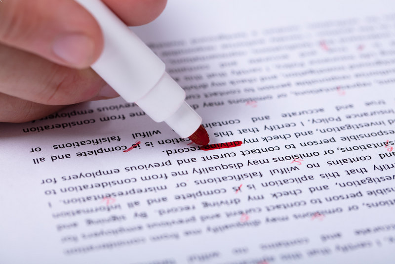 A Person's Hand Marking Error With Red Marker On Document