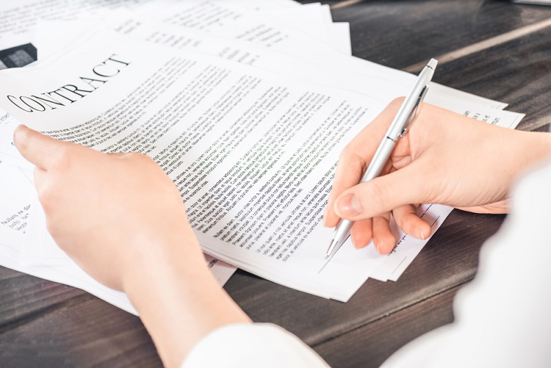 a woman signs a contract after negotiation