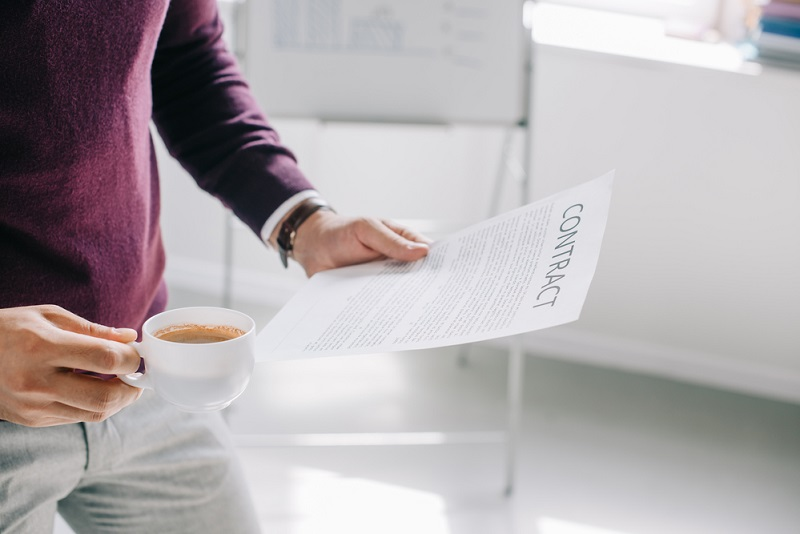 holding a contract and drinks coffee