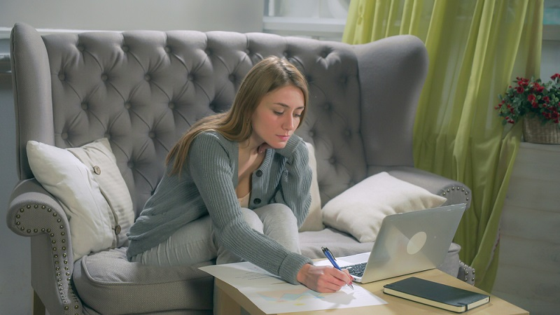 woman taking notes while working